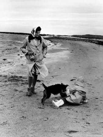 Jackie Kennedy, Wife of Sen, Walking Along Beach with Her Slicker Clad Daughter Caroline