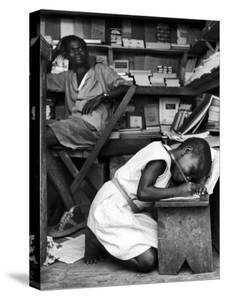 Kneeling Schoolgirl Writing on Wooden Bench. Accura, Gold Coast, Ghana by Alfred Eisenstaedt