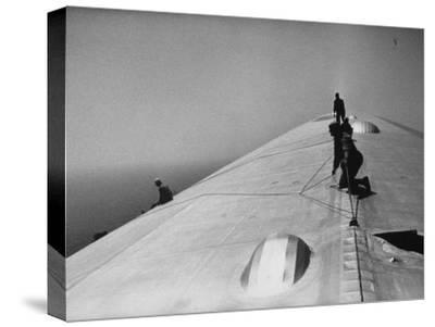 Maintenance Crewmen on Top of Graf Zeppelin repair damage caused Atlantic Ocean Storm during flight