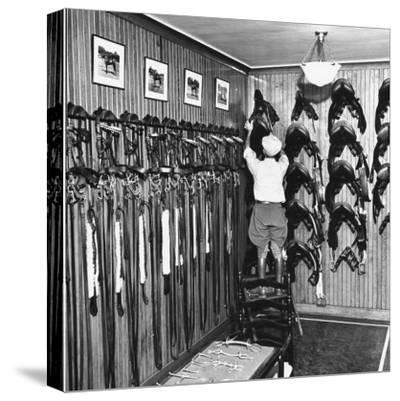 Man Checking Equipment Inside a Stable's Tack Room
