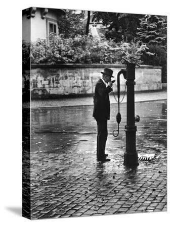 Man Drinking from Public Water Pump Fountain on Street, Frankfort-On-The-Main, Germany by Alfred Eisenstaedt