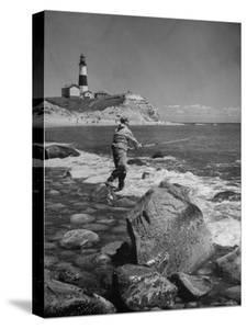 Man Fishing Off Montauk Point. Montauk Lighthouse Visible in Background by Alfred Eisenstaedt