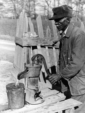 Old African American Sharecropper Dave Alexander Using Water Pump to Draw Water by Alfred Eisenstaedt