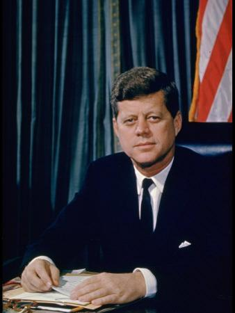 Pres. John F. Kennedy Sitting at His Desk, with Flag in Bkgrd by Alfred Eisenstaedt