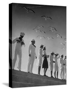 Seagulls Flying Above Group of Sailors and Waves by Alfred Eisenstaedt