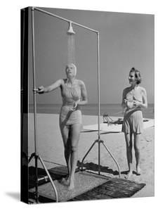 Shapely Sunbather Taking an Outdoor Shower as Woman Preparing for Her Turn, Looks On, at Beach by Alfred Eisenstaedt