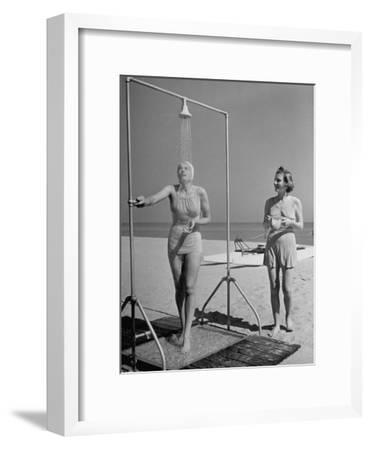 Shapely Sunbather Taking an Outdoor Shower as Woman Preparing for Her Turn, Looks On, at Beach