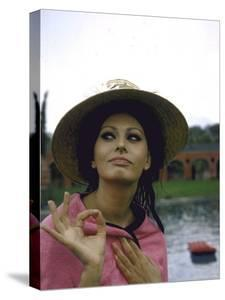 Sophia Loren Wearing a Pink Wrap and Straw Hat Out by the Pool at the Villa by Alfred Eisenstaedt
