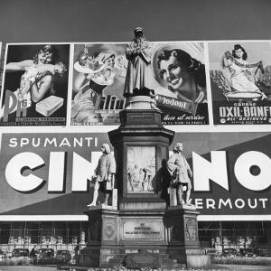 Statue of Leonardo Da Vinci on Top of Monument in Front of Giant Advertising Billboard by Alfred Eisenstaedt