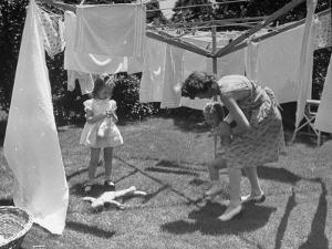 Suburban Mother Playing with Her Two Daughters While Hanging Laundry in Backyard by Alfred Eisenstaedt
