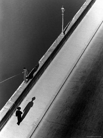 Sunday Morning Along the Arno River, a Man Fishing, and a Passerby Casting a Shadow by Alfred Eisenstaedt