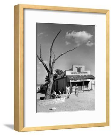 Two Boys Playing Nr. a Dead Tree as Judge Roy Langrty and a Man Walk Past a General Store