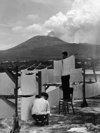 View of Mount Vesuvius from the Town of Torre Annunciata with Men Tending to Drying Pasta by Alfred Eisenstaedt