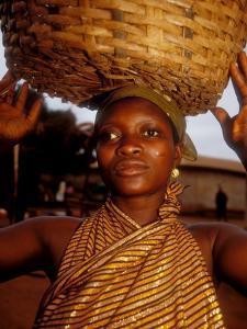 Woman Wearing Gold Fabric Dress and Carrying Basket, Kabile, Brong-Ahafo Region, Ghana by Alison Jones
