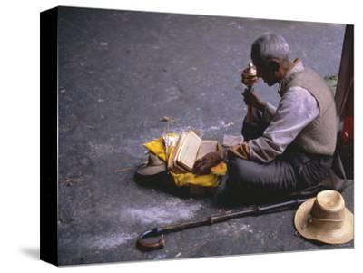 Tibetan Buddhist Pilgrim Reading Texts and Holding Prayer Wheel, Lhasa, China