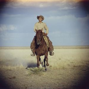 American Actor Rock Hudson Riding a Horse During Filming of 'Giant', Near Marfa, Texas, 1955 by Allan Grant