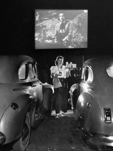 Carhop Carries Tray of Food and Drinks to Car Occupants at Drive-in Movie by Allan Grant