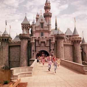Children Running Through Gate of Sleeping Beauty's Castle at Walt Disney's Theme Park, Disneyland by Allan Grant