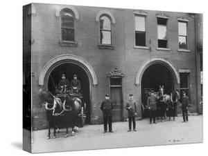 Firefighters Posing in Front of their Firehouse by Allan Grant