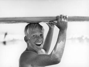 Freckled Surfer Larry Shaw Carrying Surfboard on His Head by Allan Grant