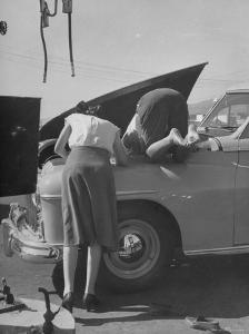 Girl Attendant Looking For Battery For Customer by Allan Grant