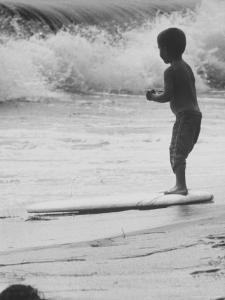 Little Boy Standing on a Surf Board Staring at the Water by Allan Grant