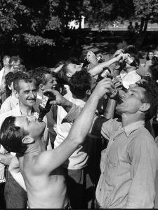Men Having a Beer Drinking Contest at the Company Picnic by Allan Grant