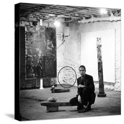 Robert Rauschenberg Sitting on His Sculpture in Studio, Among Other Paintings and Sculptures