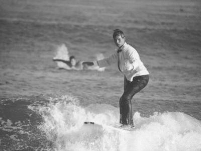 Surfer Riding a Wave While Wearing a Tuxedo