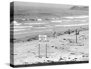 "Surfers Walking to Water Behind Sign Reading ""Official Surfing Area"" by Allan Grant"