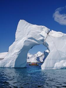Grandidier Channel, Tourists Zodiac Cruising by Arched Iceberg Near Booth Island, Antarctica by Allan White
