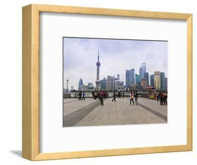 Pedestrians and Tourists on the Bund, the Futuristic Skyline of Pudong across the Huangpu River Bey