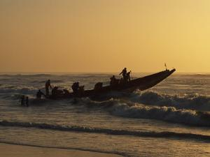 Fishermen Launch their Boat into the Atlantic Ocean at Sunset by Amar Grover