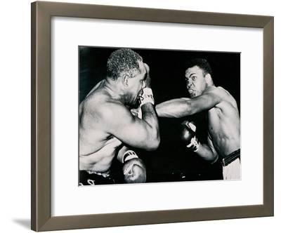 Young Cassius Clay Scores with a Left Against the Veteran Archie Moore in the First Round of the…