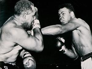 Young Cassius Clay Scores with a Left Against the Veteran Archie Moore in the First Round of the? by American Photographer