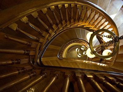 Looking Down a Spiral Staircase Past a Hanging Chandelier