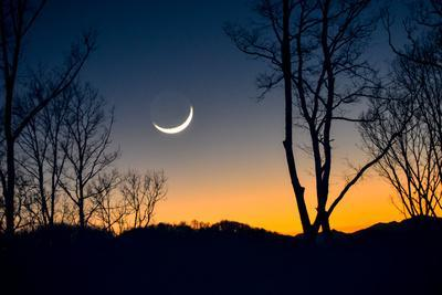 A Crescent Moon Hangs Low in the Sky over the Blue Ridge Mountains, Just after Sunset