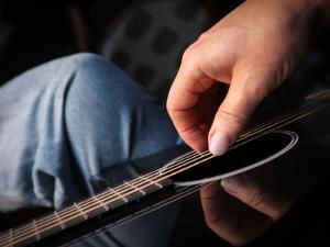 A Man Playing a Carbon Graphite Guitar Made by Rainsong by Amy and Al White and Petteway