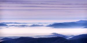 Clouds fill the valleys and hollows of the Blue Ridge Mountains during a pastel dawn. by Amy White