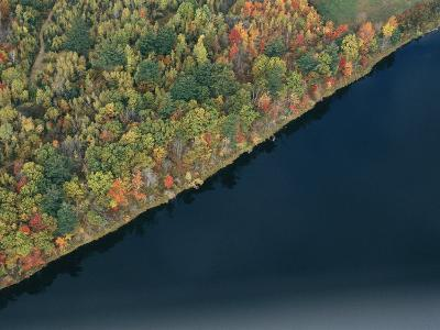 An Aerial View of a Forest in Autumn Colors Near a Body of Water-Heather Perry-Photographic Print