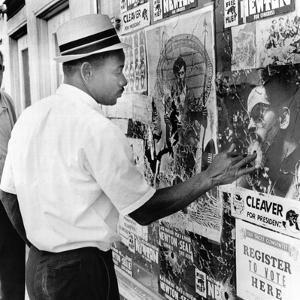An African American Pokes His Finger into a Bullet Hole in the Oakland Black Panther's Headquarters