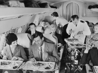 An Airline Steward and Air Hostess Serve a Roast Meal to Flight Passengers--Photographic Print