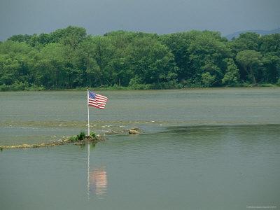 https://imgc.artprintimages.com/img/print/an-american-flag-marks-a-rock-outcrop-near-a-ferry-crossing_u-l-p4rgle0.jpg?p=0