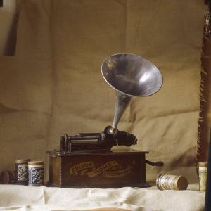 An Early Edison Phonograph Using Grooved Wax Cylinders Shown Beside the Instrument