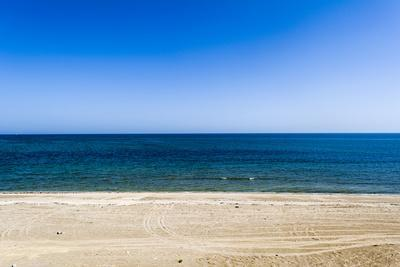 https://imgc.artprintimages.com/img/print/an-empty-flat-sandy-beach-overlooks-the-blue-seas-of-the-gulf-of-oman_u-l-pwd2to0.jpg?p=0