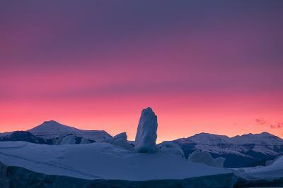 An iceberg with ice structures and mountainous coastline lit by evening sun.-Joel Sartore-Photographic Print