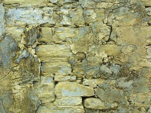 An Old Stone Wall with Crumbling Plaster