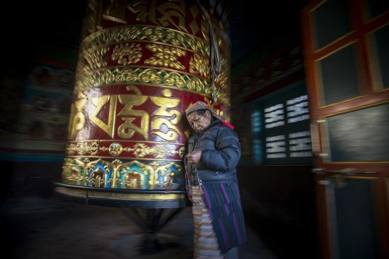 An Old Tibetan Woman Spins a Prayer Wheel While Counting Through a String of Rosary Beads-Alex Treadway-Photographic Print