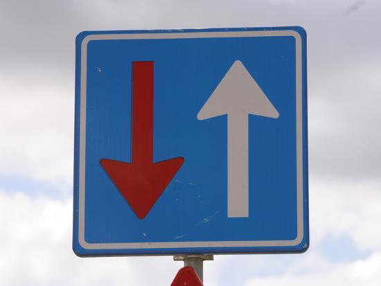 An Overcast Sky with a Blue Sign and a Red and a White Arrow--Photographic Print