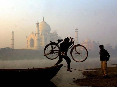 An Unidentified Cyclist Gets Down with His Cycle against the Backdrop of the Taj Mahal--Photographic Print